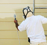 A man on a ladder uses spray gun to paint the exterior of a wooden building