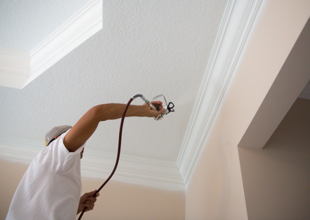 Series-Real painter spraying crown molding in a home