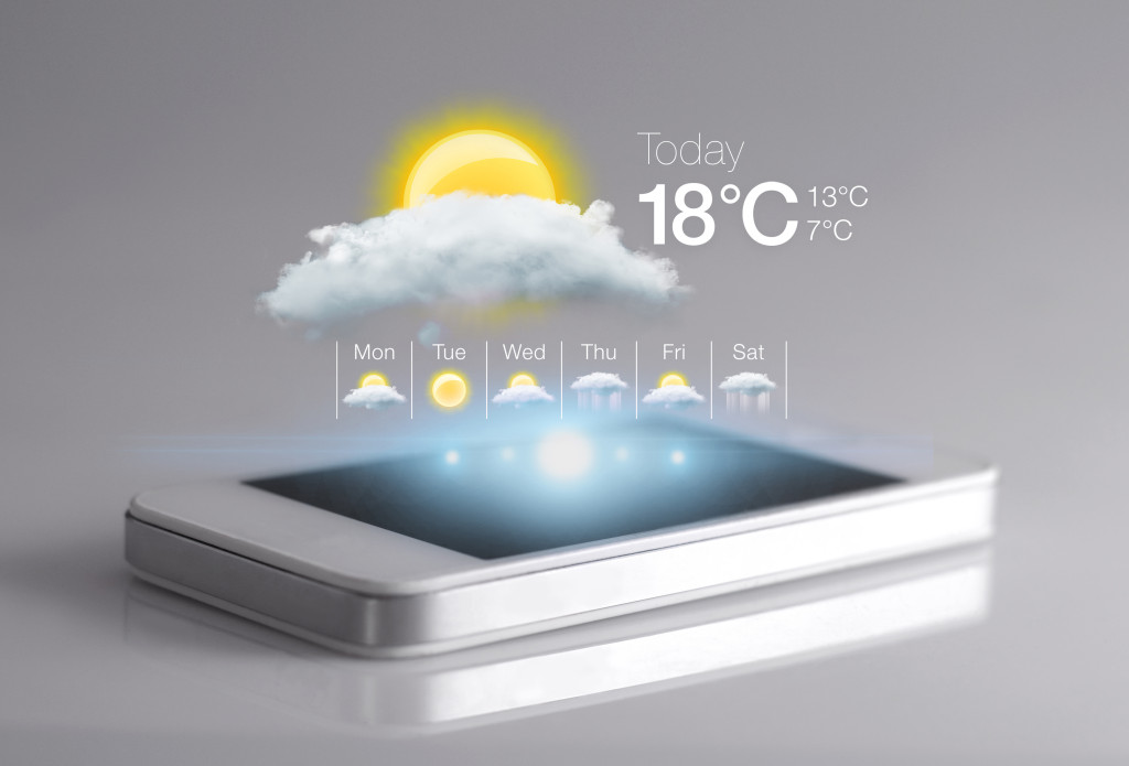 Smartphone with weather icon on light grey background.