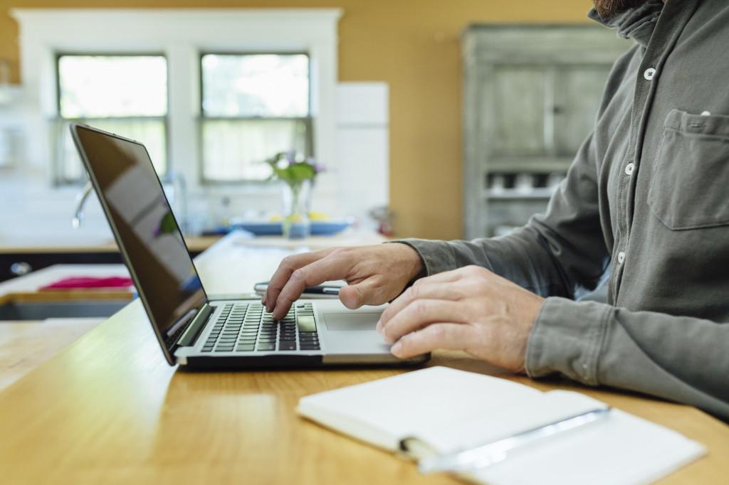 Man using laptop at home.