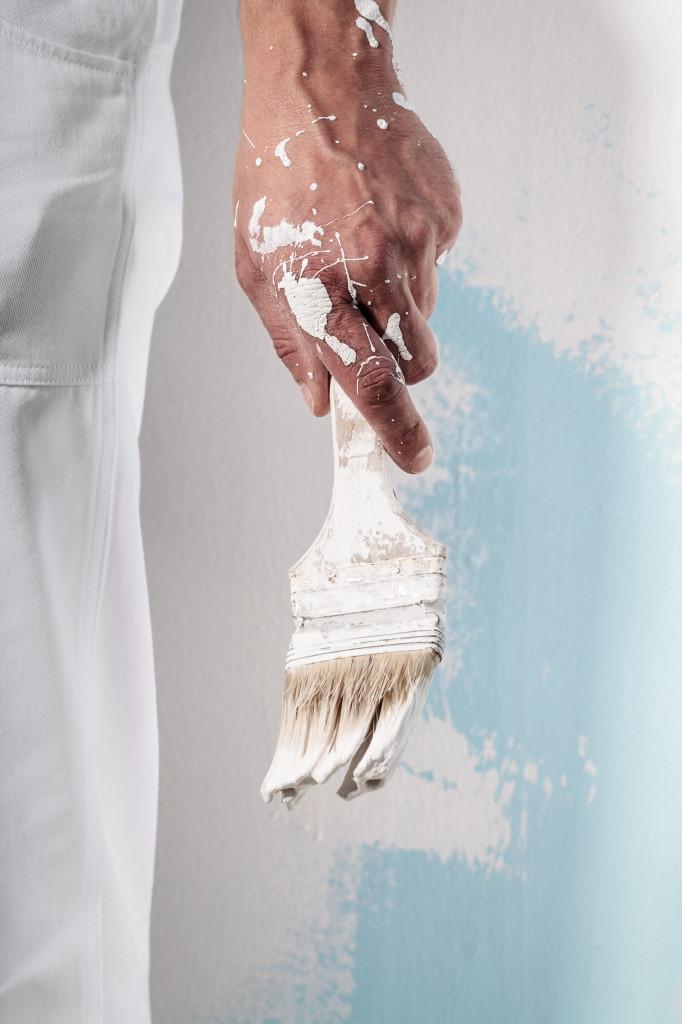 Workman Hand holding Dirty Paintbrush